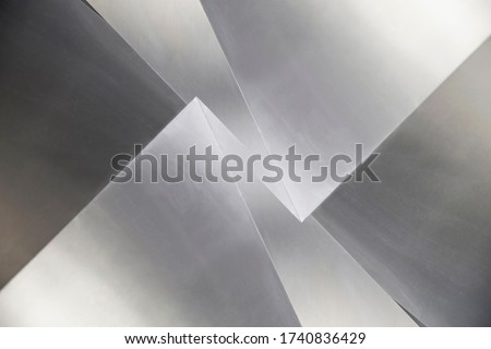 Steel panels or sheets. Abstract modern architecture exterior or interior detail. Industrial background in hi-tech style. Polygonal geometric structure in shades of metallic gray color.
