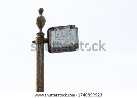 Bus stop sign, which says 'Bus Stop. On Request'. The sign is metal and rusty. It looks old, vintage and retro. It looks dirty. It's isolated against a plain background. Copy space to add text.