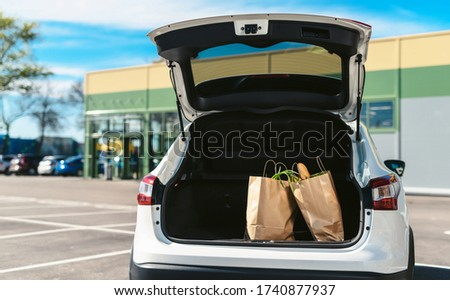 Groceries from a supermarket in a car trunk. Social distancing. Food delivery during quarantine. Paper eco bags for shopping Royalty-Free Stock Photo #1740877937