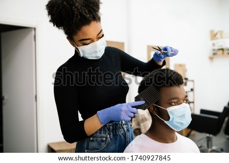 Beauty African-American hairdresser peeling and combing an African-American male client both wearing a face mask and gloves to protect himself from the coronavirus pandemic #1740927845