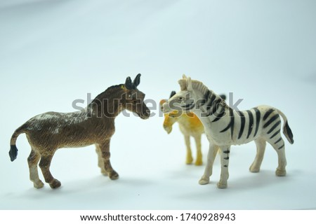 this pic show the old plastic animal toys model, it's a zebra and a donkey and a goat with white color background