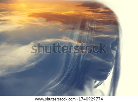 Double exposure portrait of a woman in clouds at sunset time