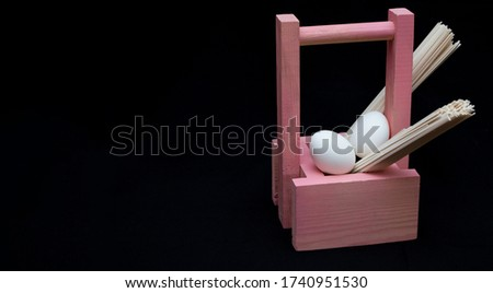 chicken eggs in a pink wooden basket and spaghetti on a black background. Easter holiday. Place for the text. Big picture. Banner.