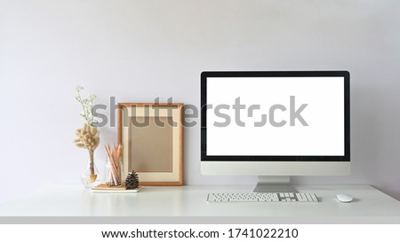 Computer monitor with white blank screen putting on workspace that surrounded by wireless mouse, keyboard, empty picture frame, pencils in glass vase and wild grass in bottle.