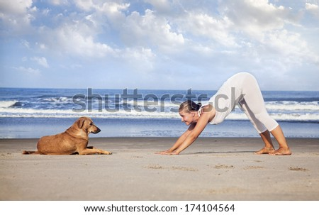 Woman in white costume doing Yoga and looking at the dog on the beach near the ocean in India #174104564