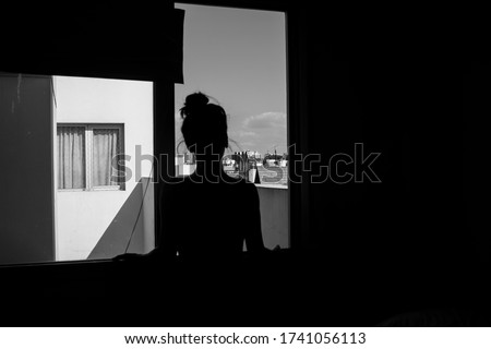 Black and white photo of woman in shadows looking trough a window staring at the city that surrounds her Royalty-Free Stock Photo #1741056113