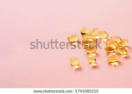 beautiful luminous gelatin capsules pills vitamins close-up on a pink background, place for text