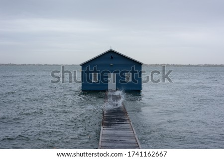 Blue boat house on the Swan River in Perth. Blue boat shed in Storm from cyclone mangga. Perth, Western Australia #1741162667