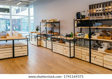 Zero waste shop interior. Wooden shelves with different food goods and personal hygiene or cosmetics products in plastic free grocery store. Eco-friendly shopping at local small businesses #1741169375