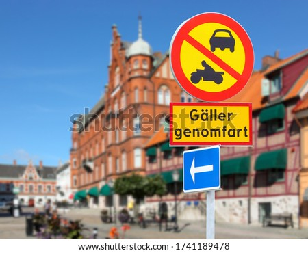 A yellow and red traffic sign in the Swedish port city of Ystad during the day in sunshine. The passage is prohibited for cars and motorbikes. Text translation: Applies to transit