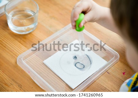 Spy game. Kids plays emotion game. Children dripping water with pipette on paper towel and finds secret picture. Activities at home. First chemistry tests. Early education.
