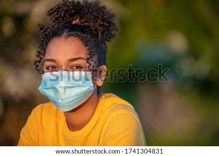 Mixed race African American teenager teen girl young woman wearing a face mask outside during the Coronavirus COVID-19 virus pandemic #1741304831