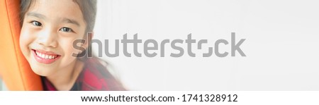 Smiling beautiful Asian kisd  with perfect smile and white teeth  in clinic, panoramic banner with copy space