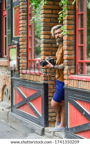 photo shooting outdoor. brutal man traveler with retro camera. photography in modern life. travel tips. professional photographer use vintage camera. bearded man hipster take photo.
