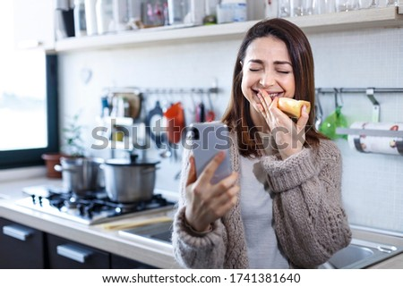 brunette girl makes a video call and laughs animatedly while eating an apple in the kitchen