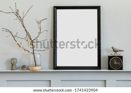 Minimalistic concept on the shelf with black mock up photo frame, dired flower in vase, black clock and elegant personal accessories at stylish home interior.