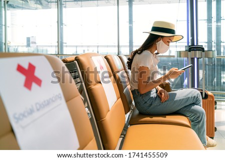 Asian female tourist wearing mask using mobile phone searching airline flight status and sit social distancing chair in airport during coronavirus or covid-19 virus outbreak a new normal concept #1741455509