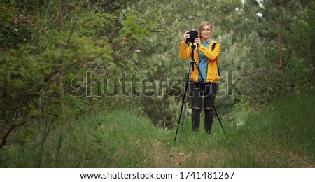 Front view of woman standing in green forest using tripod for landscape photography, she looks at camera