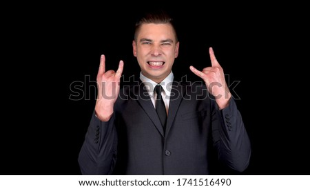 Young businessman shows a horn sign with two hands. Man in a black suit on a black background Royalty-Free Stock Photo #1741516490