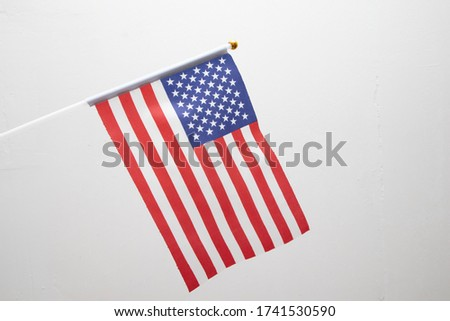 Small American flag on stick. United State of America flag on white background. USA patriotic Concept. #1741530590