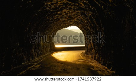 beautiful street in a rocky tunnel with an amazing sunset.  this is a street near an italian lake. Royalty-Free Stock Photo #1741537922