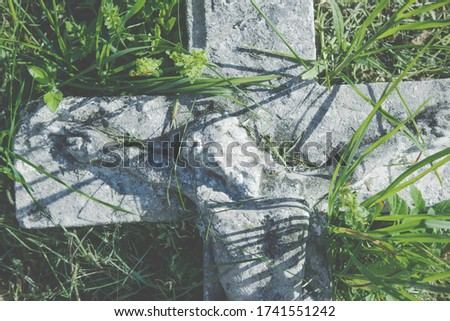Close up crucifixion of Jesus Christ. Very old and ancient stone destroyed statue in the grass. Horizontal image.