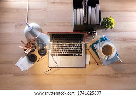 Home working place with computer lap top, coffee, lamp on the floor. Remotely at home place. Stay at home working online during the quarantine. Online education. Crisis. Empty Royalty-Free Stock Photo #1741625897