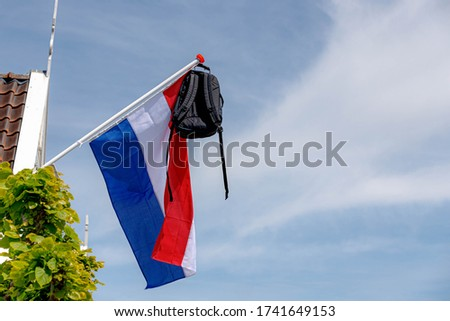 Official Netherlands flag with a school bag hanging out side the house, A tradition way in Holland when a student celebrate their graduates or Geslaagd in Dutch word, Netherlands. #1741649153
