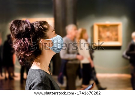 Protection from the virus. A tourist visits the sights of the Museum in a medical mask. People and pictures in the background. The concept of a viral pandemic and maintaining distance Royalty-Free Stock Photo #1741670282