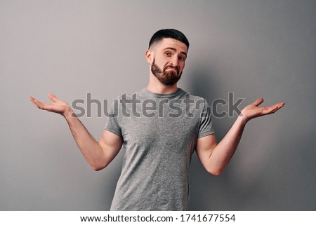 I do not know! A young man dressed in a gray T-shirt on a background of a gray wall showing helpless gesture with hands, mouth curved as if he does not know what to do. #1741677554
