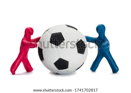 Plasticine small people soccer players red and blue with soccer ball isolated white