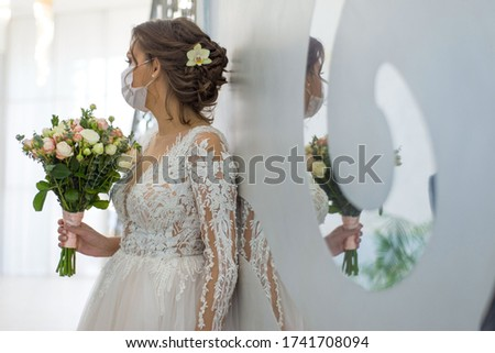wedding and coronavirus covid 19-20. The bride in a protective medical mask, and a wedding dress, stands in defocus blur, holding a wedding bouquet, reflected in the mirror of the wedding #1741708094