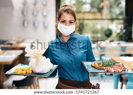 Beautiful young waitress with face protective mask working in exclusive restaurant. Coronavirus or Covid-19 concept. #1741721267