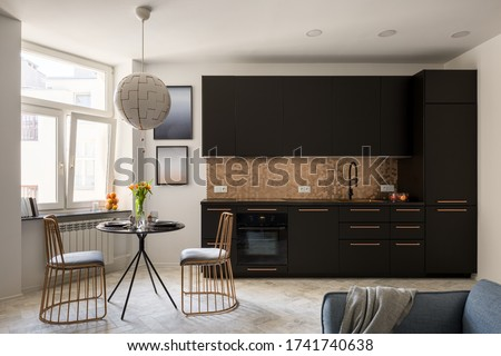 Stylish kitchen with black furniture and copper hexagon tiles with black, dining table and two copper chairs #1741740638