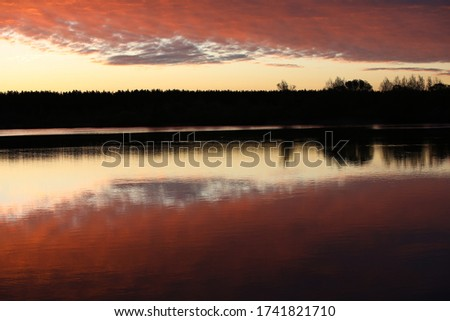 Mirror image of pink light sky with bright burning crimson clouds in the lake at dawn.The illuminated black forest on the horizon is copied in the calm water.A glossy picture in the twilight.Russia