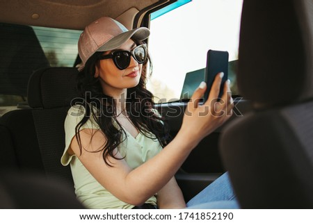 Young woman using mobile app traveling by car. Information technology, travel, smart application #1741852190