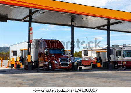 Big red semi-truck at fueling station truck stop. Truck Driver washes the windshield of a large truck at a gas station. Transportation, gas station. #1741880957