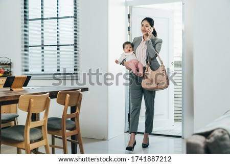 elegant chinese businesswoman just arriving home with kid is answering her customer's call. happy asian career woman carrying infant is having peaceful conversation with nanny on cellphone.