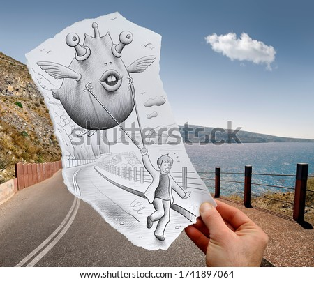 Funny fantasy creature flying held with a rope by running boy drawn on a hand held piece of paper with seascape in Santorini in the photo background. Mixed media image.