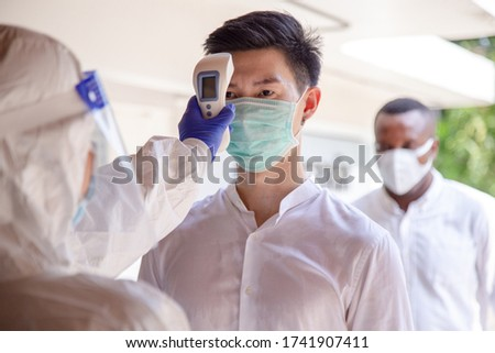 Social distancing concept. Officer wearing a respirator mask to use infrared forehead thermometer to check fever body temperature for virus symptoms. Respiratory diseases such flu covid19, coronavirus Royalty-Free Stock Photo #1741907411