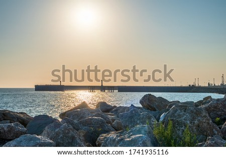 Large stones and rocks against the background of the seaport. Breakwater of large stones on the sea coast. Clear sky and bright sunset at sea port with a breakwater and a lighthouse #1741935116