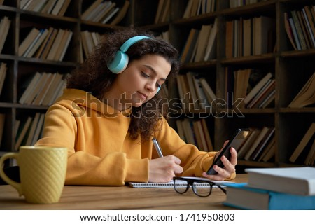 Latin teen girl wear headphones hold phone online learning in mobile app. Hispanic college student using smartphone watching video course, zoom calling making notes in workbook sit in library campus. #1741950803