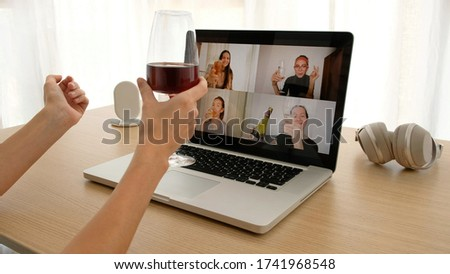 Crop female sitting with glass of wine at table and making video call via laptop with girlfriends while having remote party during coronavirus outbreak #1741968548