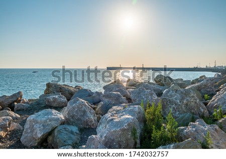 Large stones and rocks against the background of the seaport. Breakwater of large stones on the sea coast. Clear sky and bright sunset at sea port with a breakwater and a lighthouse #1742032757
