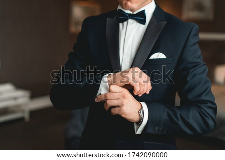 A man fastens cufflink on the white shirt. Close up of a man hand wearing a white shirt and cufflinks. Royalty-Free Stock Photo #1742090000