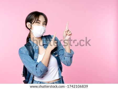 Young happy Asian woman pointing finger hands up to copy space wearing hygienic mask to prevent infection corona virus she jean jacket and carry backpack shirt shoot in isolated on pink background #1742106839