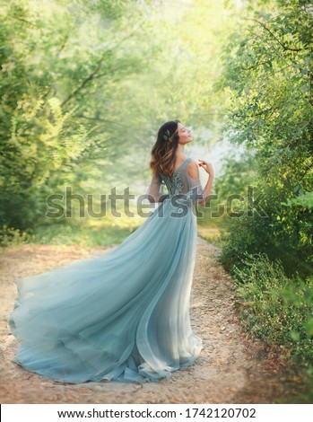 fairy tale princess in light summer blue, turquoise dress standing in park. Happy Woman walks towards wind. fashion model posing. fantasy image girl goddess. flying long hem of dress. nymph of forest #1742120702