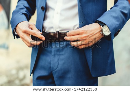 Groom in blue pants and a white shirt fastens his leather belt. grooms mourning. Wedding details. Royalty-Free Stock Photo #1742122358