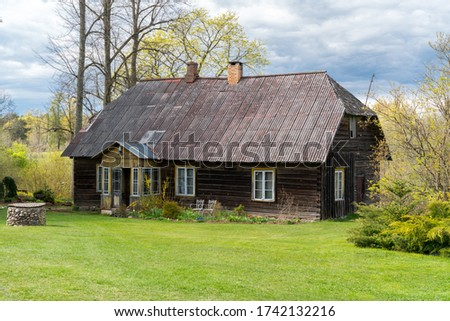 Amazing restored old traditional farm house in Mikko farm South Estonia. Beautiful garden around historic timber construction homestead building. Dark color log cabin as a old farm shed.