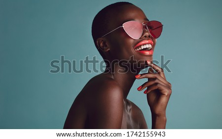 Close up shot of beautiful woman in sunglasses and red lips against grey background. African female model with funky sunglasses. #1742155943